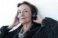 Mujer mayor que escucha la música Fotografía de archivo libre de regalías