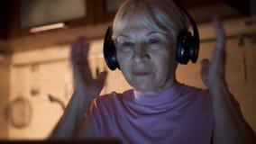 Mujer mayor que escucha la música en los auriculares inalámbricos mientras que usa el ordenador portátil en la noche de Ministeri almacen de metraje de vídeo