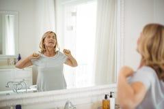 Mujer mayor que estira delante del espejo Fotos de archivo libres de regalías