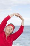 Mujer mayor que estira el océano del ejercicio Imágenes de archivo libres de regalías