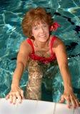 Mujer mayor que estira en la piscina Fotografía de archivo