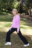 Mujer mayor que estira en parque Foto de archivo libre de regalías