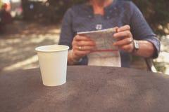 Mujer mayor que estudia el mapa y que come café Imagen de archivo