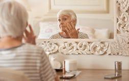 Mujer mayor que examina su cara en un espejo fotos de archivo libres de regalías