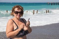 Mujer mayor que fotografía por el teléfono en la playa Imágenes de archivo libres de regalías