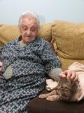Mujer mayor que frota ligeramente su gato Imagen de archivo