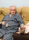 Mujer mayor que frota ligeramente su gato Fotos de archivo
