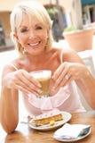 Mujer mayor que goza del café y de la torta imagen de archivo libre de regalías