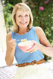 Mujer mayor que goza del tazón de fuente de cereal de desayuno Imágenes de archivo libres de regalías