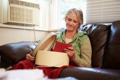 Mujer mayor que guarda la manta inferior caliente con la caja de la memoria Fotos de archivo libres de regalías