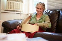 Mujer mayor que guarda la manta inferior caliente con la caja de la memoria Foto de archivo libre de regalías