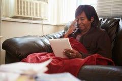 Mujer mayor que guarda la manta inferior caliente con la fotografía foto de archivo libre de regalías