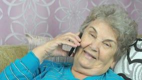 Mujer mayor que habla con el amigo en el teléfono móvil almacen de metraje de vídeo