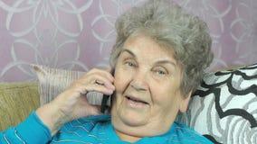 Mujer mayor que habla con la hija en el teléfono móvil almacen de metraje de vídeo