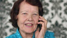 Mujer mayor que habla en el teléfono almacen de video