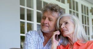 Mujer mayor que habla en el teléfono móvil al lado de su hombre en el sofá 4k almacen de metraje de vídeo