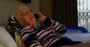 Mujer mayor que habla en el teléfono móvil en el dormitorio 4k almacen de video