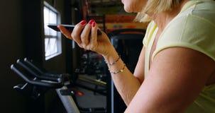 Mujer mayor que habla en el teléfono móvil durante ejercicio en el estudio 4k de la aptitud metrajes