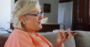 Mujer mayor que habla en el teléfono móvil en la sala de estar 4k almacen de video