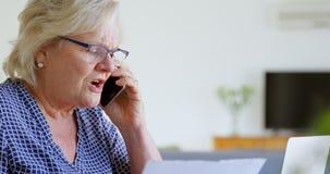 Mujer mayor que habla en el teléfono móvil en la sala de estar 4k metrajes