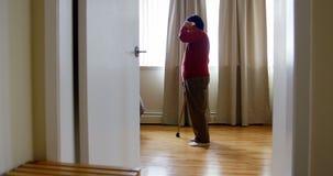 Mujer mayor que habla en el teléfono móvil en sala de estar almacen de metraje de vídeo