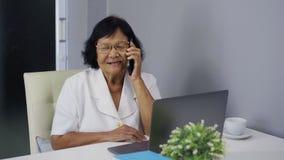 Mujer mayor que habla en el teléfono móvil y que usa el ordenador portátil almacen de metraje de vídeo