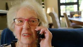 Mujer mayor que habla en el tel?fono m?vil en sala de estar almacen de metraje de vídeo