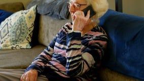 Mujer mayor que habla en el tel?fono m?vil en sala de estar metrajes