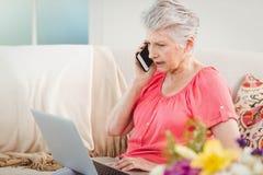 Mujer mayor que habla en el teléfono y que usa el ordenador portátil Fotos de archivo libres de regalías