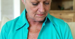 Mujer mayor que hace compras en línea usando el ordenador portátil con la tarjeta de crédito en la sala de estar metrajes