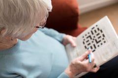 Mujer mayor que hace crucigrama en casa Imágenes de archivo libres de regalías