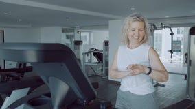Mujer mayor que hace deportes en una rueda de ardilla en el gimnasio usando un reloj cardiio de los deportes imágenes de archivo libres de regalías