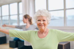 Mujer mayor que hace ejercicio de los aeróbicos en el gimnasio Foto de archivo libre de regalías