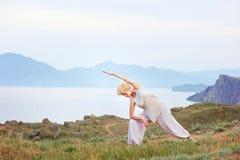 Mujer mayor que hace ejercicios de la yoga Imagenes de archivo