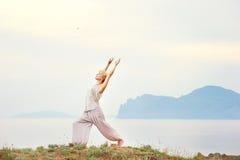 Mujer mayor que hace ejercicios de la yoga Foto de archivo