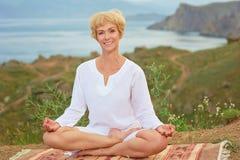 Mujer mayor que hace ejercicios de la yoga Imagen de archivo libre de regalías