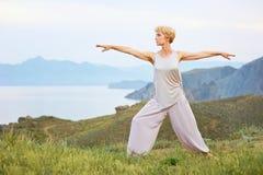 Mujer mayor que hace ejercicios de la yoga Foto de archivo libre de regalías