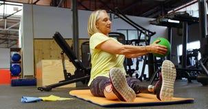 Mujer mayor que hace ejercicios oblicuos en la estera 4k del ejercicio almacen de metraje de vídeo