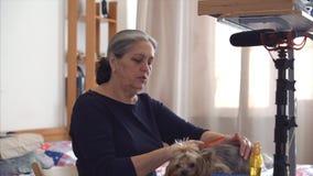 Mujer mayor que hace el blog video sobre su perro, wonam que mira periódicamente en la leva metrajes