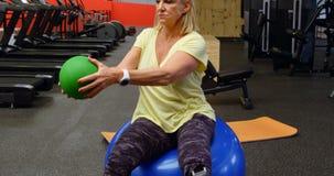 Mujer mayor que hace entrenamiento del ABS con la bola 4k del ejercicio almacen de metraje de vídeo