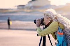 Mujer mayor que hace fotografía en una playa en la Florida imagen de archivo libre de regalías