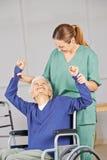 Mujer mayor que hace la fisioterapia en clínica de reposo foto de archivo