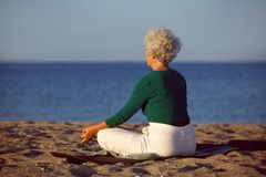 Mujer mayor que hace la meditación de la yoga en la playa fotografía de archivo