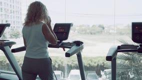 Mujer mayor que hace la rueda de ardilla en el gimnasio y que habla en el teléfono imagen de archivo libre de regalías