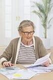 Mujer mayor que hace papeleo imagenes de archivo