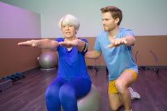 Mujer mayor que hace terapia física en bola Imagen de archivo libre de regalías