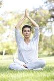 Mujer mayor que hace yoga en parque Imagen de archivo
