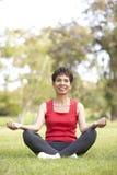Mujer mayor que hace yoga en parque fotos de archivo