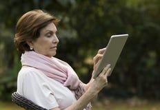 Mujer mayor que hojea en la tableta de Digitaces en un jardín Fotos de archivo