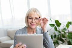 Mujer mayor que hojea en la tableta digital, leyendo noticias fotografía de archivo libre de regalías